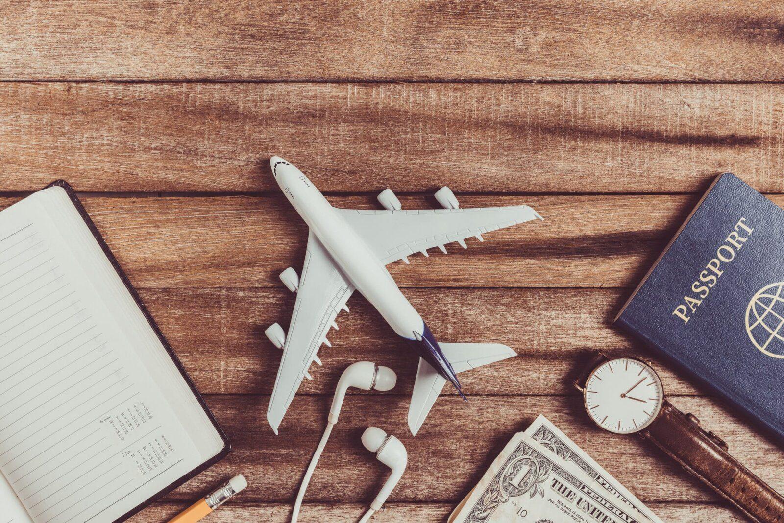 Plane, money and passport on table